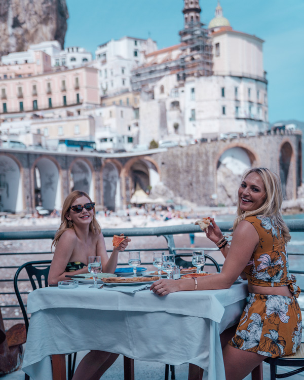 two blonde girls eating pizza in Atrani on the amalfi coast