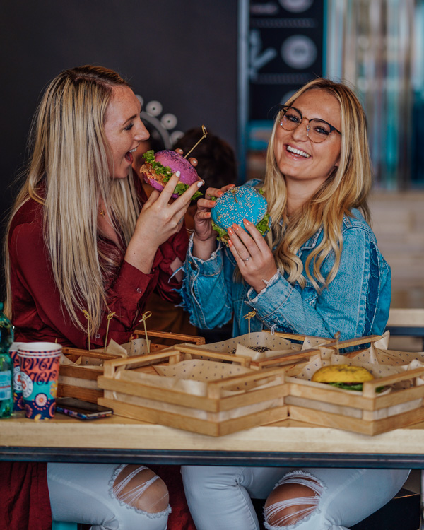 two blonde girls eating vegan burgers at flower burger in rome